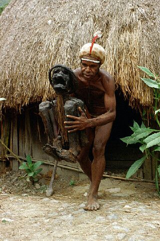 A Dani tribesman carries the mummified corpse of a Dani chief out of a hut in the Baliem Valley, Irian Jaya, Republic of Indonesia. |  © Charles & Josette Lenars