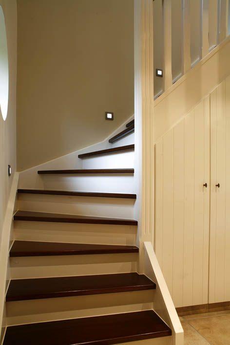 Geschilderde houten trap met onderbouwkasten in lak.