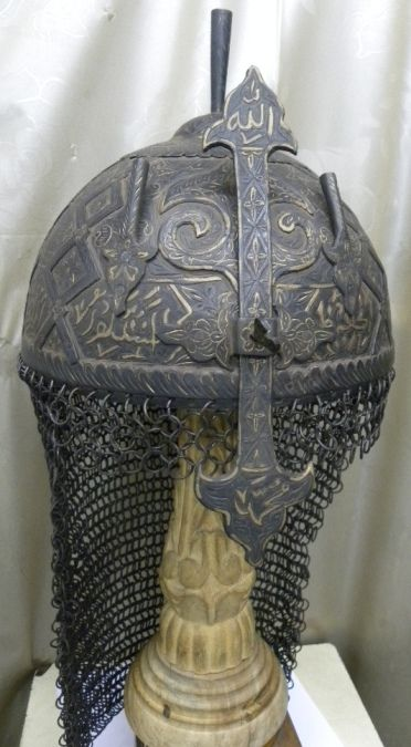 INDO PERSIAN ISLAMIC WARRIOR IRON STRIP HELMET DEMON DEVIL FACE [TC/341] Out standing rare Indo Persian Islamic empire khula khud battle warrior helmet . Has unusual demon devil face.Helmet has Arabic calligraphy. A warrior would have worn this helmet he would have been confident of being safeguarded in battle by the writing around helmet's rim .