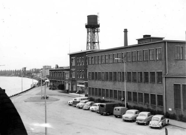 Gezicht op het parkeerterrein met een gedeelte van de kantoorgebouwen van de fabriek van de N.V. Nederlandse Staalfabrieken DEMKA voorheen J.M. de Muinck Keizer (Havenweg 7) te Utrecht, vanaf de spoorbrug over het Amsterdam-Rijnkanaal, uit het zuidzuidwesten; van rechts naar links het centrale magazijn, het hoofdkantoorgebouw en het gebouw met loonadministratie en personeelsruimte; daar bovenuit de watertoren en links de bocht in het Amsterdam-Rijnkanaal. 1955-1965