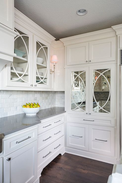Lovely kitchen with glass-front upper cabinets with trim moldings and inset lower cabinets paired with gray countertops and marble beveled subway tiled backsplash next to built-in pantry with mirrored doors.
