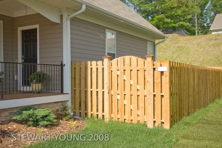 Install a Shadow Box Fence around the back yard coming off the back corners of the house with a gate like the one in the picture on one side.