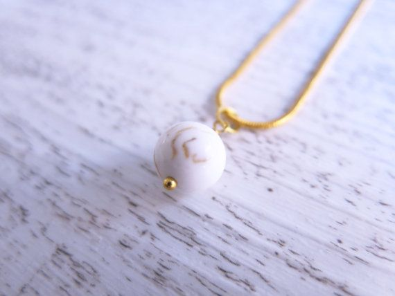 This beautiful necklace is made from a stunning sphere of howlite suspended from a 24k gold plated chain.  White Howlite is a stone of