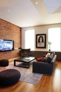 Eine Backstein-Wand mit einem Wand-TV ist die zentrale Anlaufstelle für dieses Wohnzimmer mit neutralen Farben verziert. Foto: Valerie Pasquiou Interieur + Design, inc