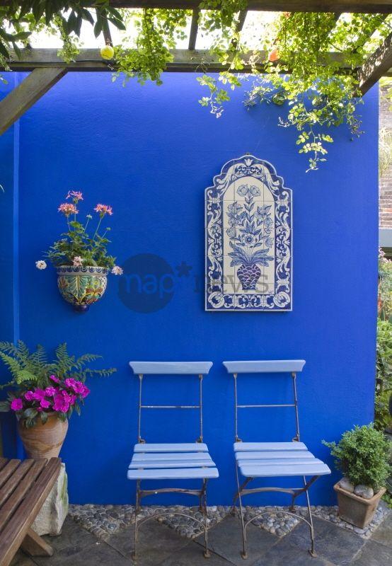 Jardin de cour, jardin de ville, jardin méditerranéen. Pergola. Coin repos, chaise de jardin sur terrasse dallée. Ardoise, galet. Carrelage mural peint à la main, panneaux d'azulejos sur un mur de couleur bleu. Jardin de Karla Newell, Brighton, Angleterre
