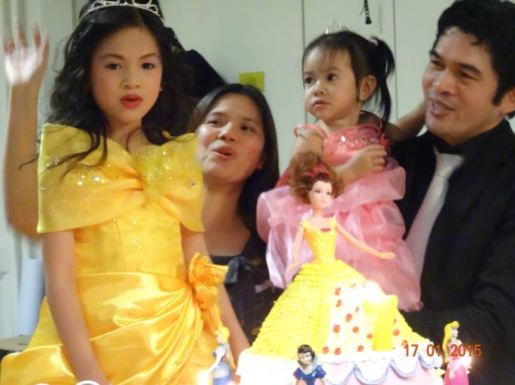 The bday girl blowing of the candles with her Belle gown.