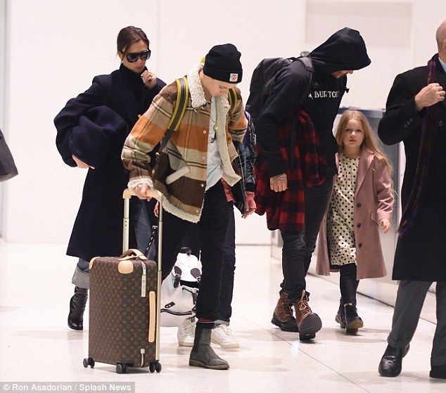 Walk this way: Former footballer David, 42, attempted to remain low-key as he donned a black Burton hoodie for the occasion while he held his six-year-old daughter Harper's hand through the terminal