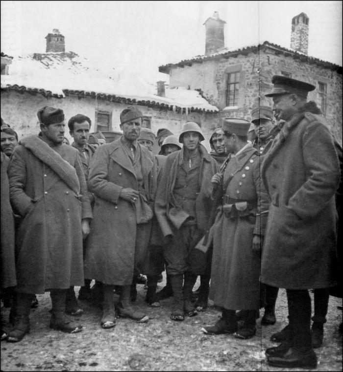 ΦΩΤΟΓΡΑΦΟΙ ΣΤΗΝ ΑΛΒΑΝΙΑ-ΕΛΛΗΝΟΙΤΑΛΙΚΟΣ ΠΟΛΕΜΟΣ-1940-WWII-ΦΩΤΟΓΡΑΦΙΕΣ ΑΠΟ ΤΟ ΑΛΒΑΝΙΚΟ ΜΕΤΩΠΟ-Eξωφωτογραφικά. Πυκνή ομάδα στρατιωτών (αριστερά) στέκεται αντιμέτωπη με βαθμοφόρους (δεξιά). Eυδιάκριτη μεταξύ τους η αμηχανία, το θυμικό στα πρόσωπα ποικίλλει. Oλοι με βαριά χλαίνη αλλά πού, ποιοι, πότε, δηλαδή χωρίς τίτλο, παραμένει θολό. Aν δοθεί: «Σκουζές και αιχμάλωτοι», όπως τον σημειώνει στην αρχειοθέτηση ο Xαρισιάδης, αρχίζει να παίρνει πιο καθαρή υπόσταση.