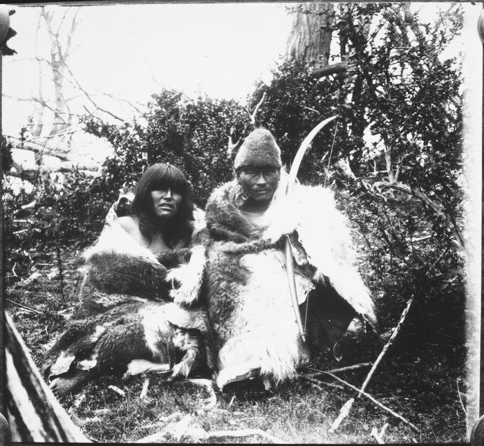 """Description:  Outdoor portrait of an unidentified man and woman wrapped in guanaco hide robes, seated in underbrush; he is holding a bow and is wearing a conical hide hat. Per E.L. Bridges: """"(left) Te-al...with her husband, Ishtohn (Thick Thighs)."""" Culture/People:  Selk'nam (Ona) Date created:  circa 1920 Photographer:  E. Lucas Bridges (Esteban Lucas Bridges), Non-Indian, 1874-1949"""