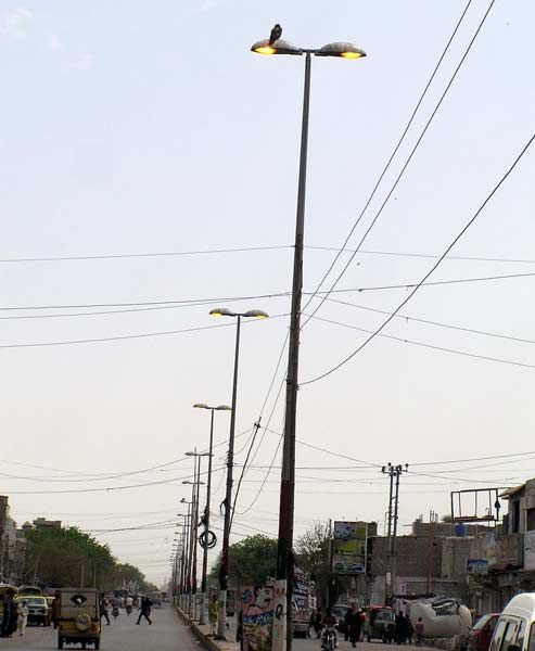 Streetlights are seen on in daylight at a road while residents of city are facing electricity load-shedding needs the attention of electric supply company (KESC), in New Karachi on Friday, April 20, 2012.