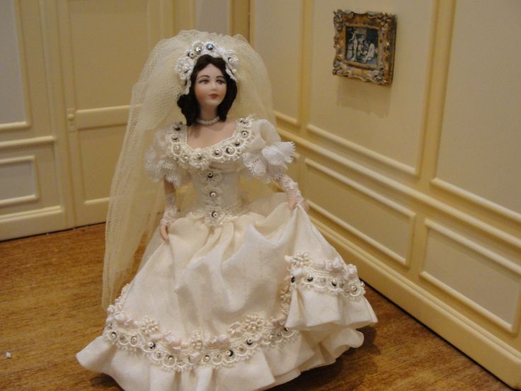 Jacqueline Polier - porcelain bride - he gown has a wide full skirt embellished with tiny beads-pearls and rhinestones. She wears white lace half-sleeves and is holding her gown in her hands. The bodice is likewise done with beads-rhinestones and a darker contrasting bead. She has brown hair and wears an elaborate matching headpiece with a long net veil. Her undergarments are just as fine as her gown with multiple petticoats and beautifully finished pantaloons. sold on ebay for $329