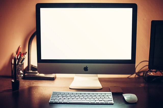 Front-view iMac on a wooden desk, next to Apple keyboard and mouse, pens and lamp. Place your iOS app screenshot in this image without Photoshop on Picapp.net #iMac #office #business #mockup