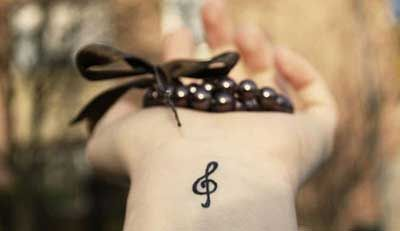 Little wrist tattoo of a treble clef.
