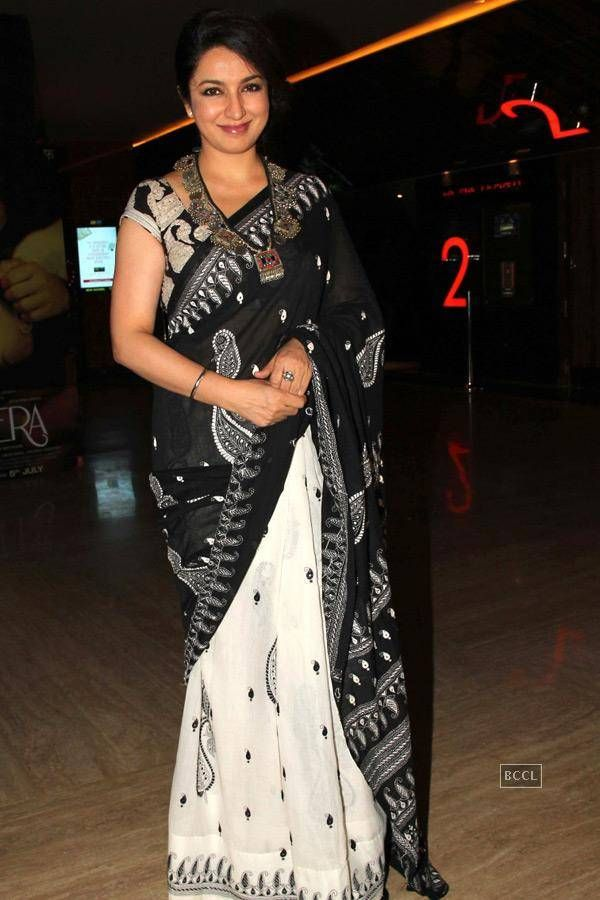 Tisca Chopra in beautiful black and white designer half and half saree. Paired with black designer mini sleeves saree blouse with wide neck pattern. Embellished with patch work all over.