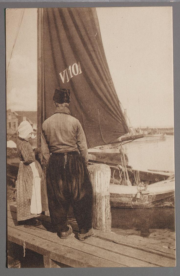 Op den uitkijk. - Volendam. Volendammer man met ruige muts op de rug gezien met meisje in katoenen jak en rok met motiefjes, hul en schort bij de VD 101. Een kuilgewicht hangt aan de zijkant van de botter. 1900-1925 #NoordHolland #Volendam