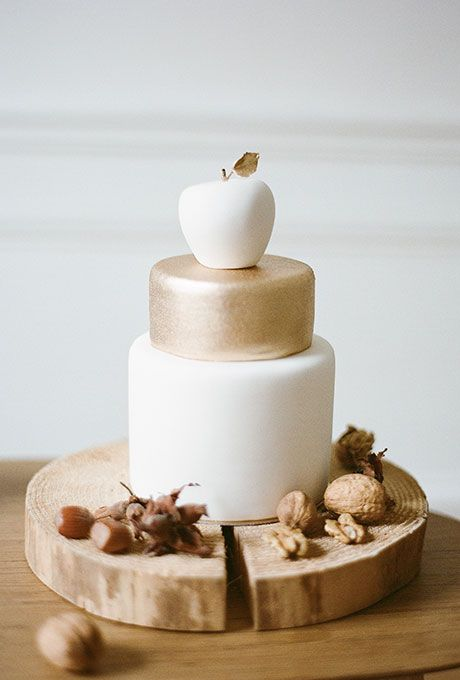 Brides: A White-and-Gold Cake with Apple Topper. A two-tiered white-and-gold wedding cake topped with an apple, created by Sugarplum Cake Shop.