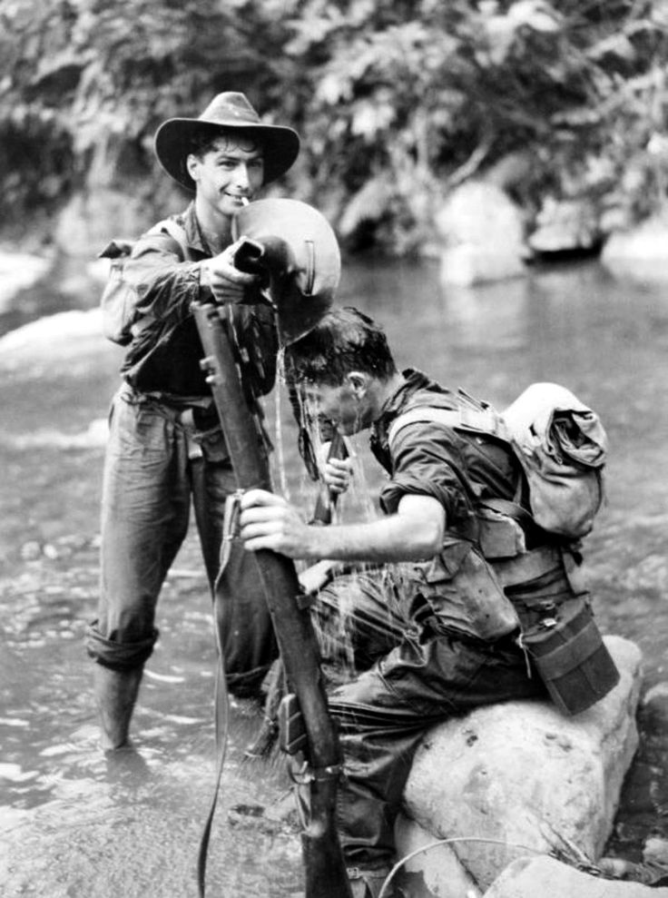 Two Australian soldiers cool off in a stream after a patrol in the Wonginara…