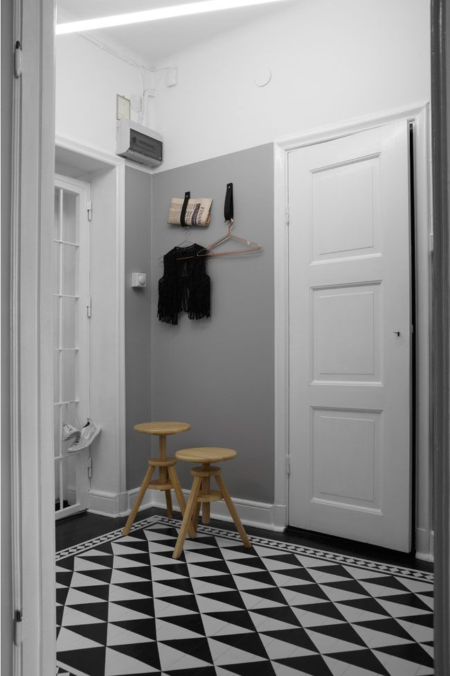 Grey walls, white panelling and geometric black and white tiles