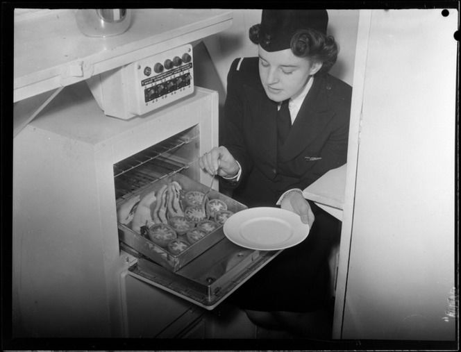 Tasman Empire Airways stewardess [Mrs Colley?] preparing bacon and tomatoes 1956