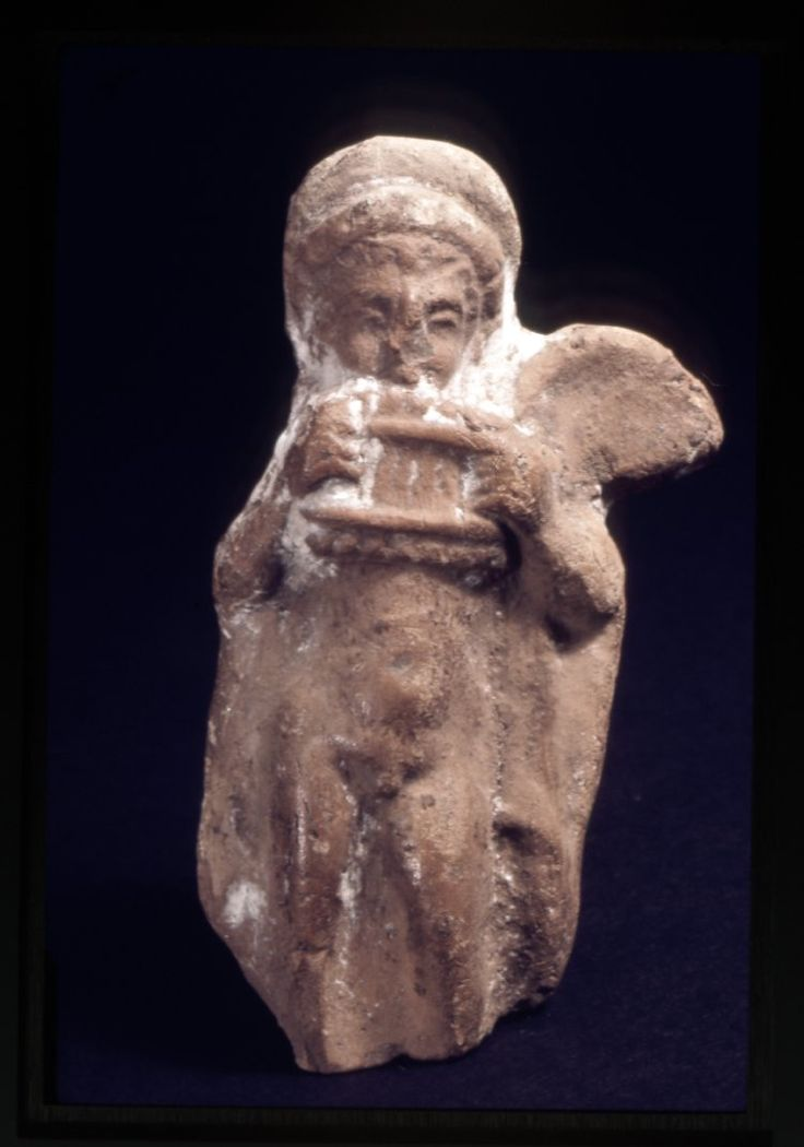 Baked clay figurine of nude winged male in a cloak playing a set of Pan-pipes; originally covered in a white slip which acted as a ground for applied coloured pigments; one wing missing and much of the slip worn away. Culture/period Hellenistic