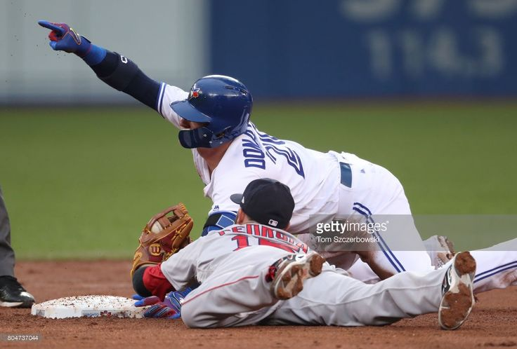Josh Donaldson #20 of the Toronto Blue Jays reacts after sliding into second base with a double in the third inning during MLB game action as Dustin Pedroia #15 of the Boston Red Sox makes the late tag at Rogers Centre on June 30, 2017 in Toronto, Canada.