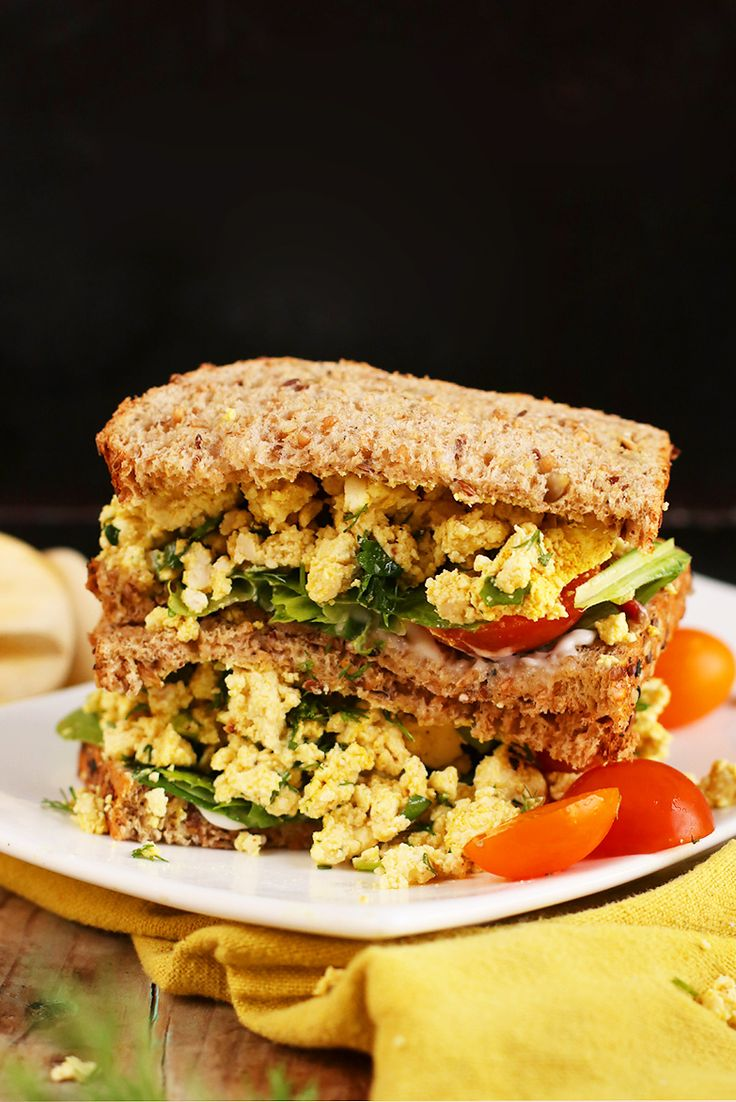 This refreshing vegan egg salad sandwich is made with scrambled tofu mixed with fresh herbs and spices and topped with mixed greens and fresh tomatoes.