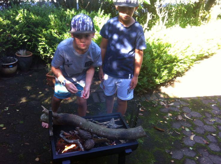 Young chefs preparing fire gor shashlyk