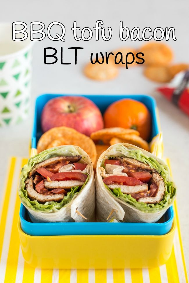 Tofu bacon BLT wraps cut in half and served in a yellow lunchbox with fruit