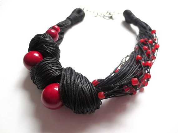 This asymmetric necklace is made of black natural linen cord , 4 red round tagua nut beads with gloss finish and small indo-pacific red glass beads.