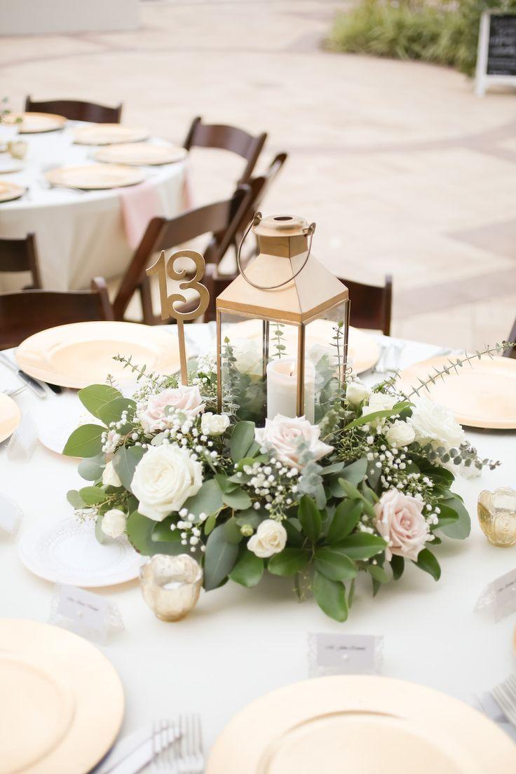 Rustikale nautische Hochzeit im Freien runden Tisch Dekor mit Gold Hurricane Laterne und niedrige weiße Rose mit Grün Herzstück, Gold Ladegeräte und Tee Kerzen, hellblaue Tischdecke und rosa Bettwäsche und Braune Holz Klappstühle