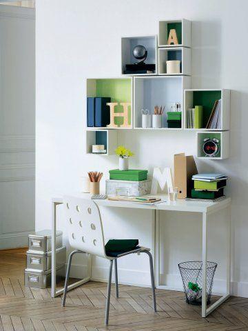 Des carrés en bois blanc avec fond coloré sont accrochés au mur en guise d'étagères