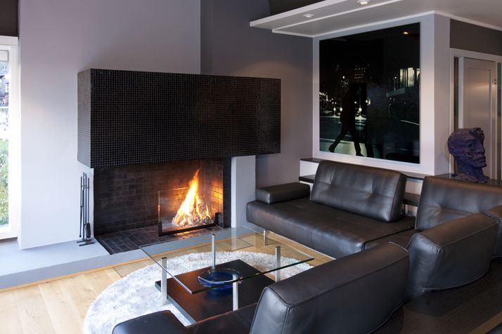 Exclusive atmosphere in this black and silver decorated living room, warmed up by the fireplace. Interior architecture | Ramsoskar