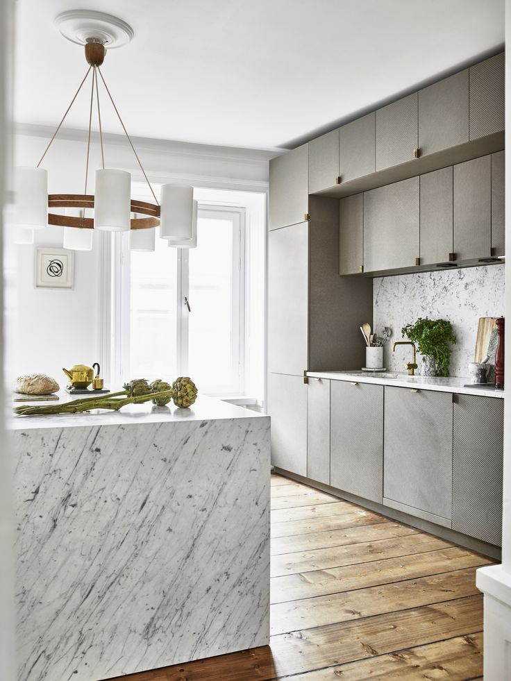 marble waterfall edge, wood floors, natural light...what is there not to love in this kitchen