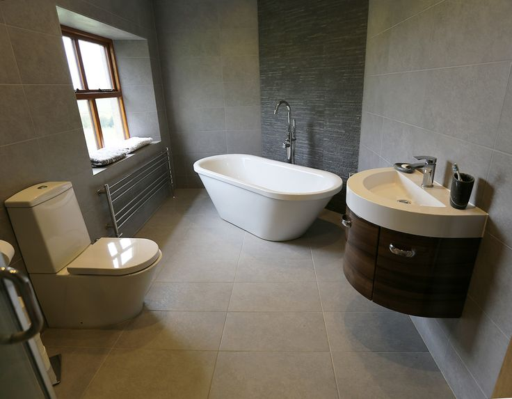 bathroom, stand alone bath, slate tile feature behind tub, walnut curved sink unit and half moon sink, grey porcelain tiles