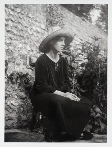 Vanessa Bell seated on a 'Prie-Dieu' chair designed by Duncan Grant, outside the studio at Charleston farmhouse circa 1922-24