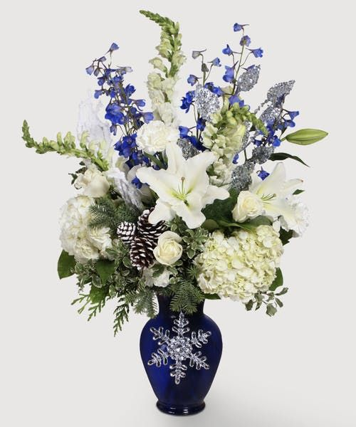 This royal blue, glimmering silver, and white arrangement brings to mind the beautiful color contrast of a snowy evening.  Curl up and stay warm, bringing the atmosphere of a silent night into your home. #stadiumflowers