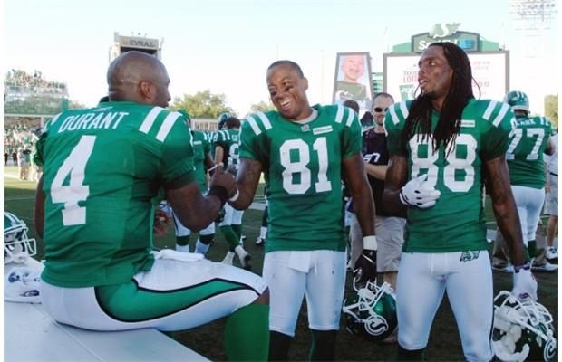 Saskatchewan Roughriders quarterback Darian Durant, slotback Geroy Simon and wide receiver Taj Smith congregate after a successful play at a game held at Mosaic Stadium in Regina, Sask. on Sunday Sept. 1, 2013.