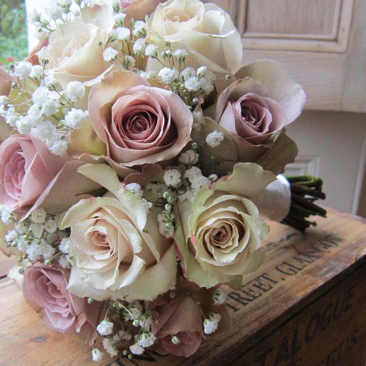 Vintage Lilac Amnesia roses with cream roses and white gyp mixed in .