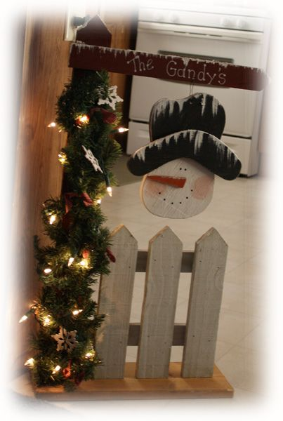 sign with picket fence and snowman