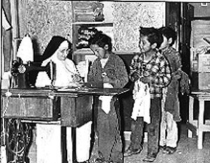 """Learning sewing at St. Mary's Mission School in Omak, Washington. Father Stephen de Rouge (former French Count de Rouge of the Chateau des Rues) began St. Mary's Mission in 1886 in a small """"log house without a floor, window or chimney..."""". In 1887 he moved to land offered by chief Smitkin along Omak Creek."""