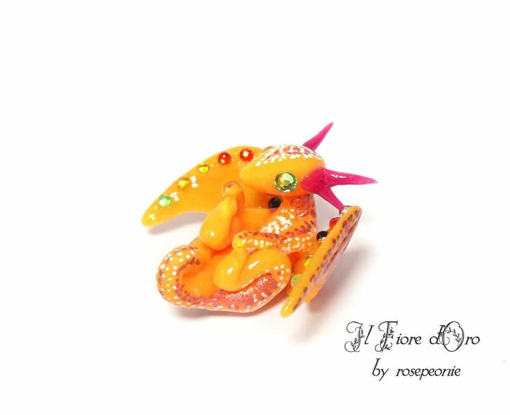 Orange baby Chameleon Dragon  I took the design for the gift critters and enriched it a bit ☺️ Look at all the shiny rhinestones! Isn't he cute, holding his chubby feet? Plus I love this colour; it reminds me of mango icecream  Cold porcelain clay, rhinestones, varnish. Approx 2,5 cm long.   Up for sale tomorrow, Tue 16th August, in my Etsy!  #dragon #dragons #chameleon #shopsmall #smallbusiness #sculpture #miniature #cutie #clay #coldporcelain #fantasy #collector #beastie