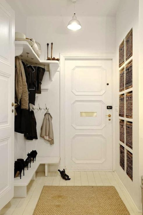 Fantastic mud room with decorative moldings on door, industrial pendant, seagrass rug, shoe rack and built-ins with woven storage baskets.