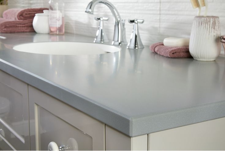 Silver grey shimmer solid surface bathroom worktops with a chamfered edge detail #fittedfurniture #bathroomfurniture #worktops #myutopia