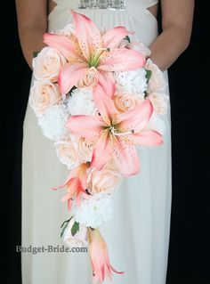 Cascading Coral and Peach Wedding Bouquet with white carnations, peach roses and accented with beautiful Coral Lillies.  Silk Wedding Flower Packages starting as low as $100