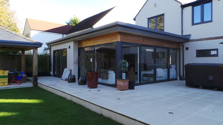 Single storey contemporary extension to form new Kitchen / Family room. Modern flat roof design featuring Aluminium sliding doors and timber cedar boarding