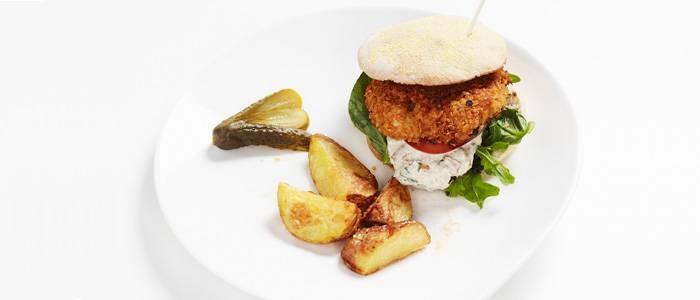 Hemlagad krispig kycklingburgare med nybakt hamburgerbröd, fräscha grönsaker, baconcreme och ugnsrostad klyftpotatis - recept från Lantmannen.se