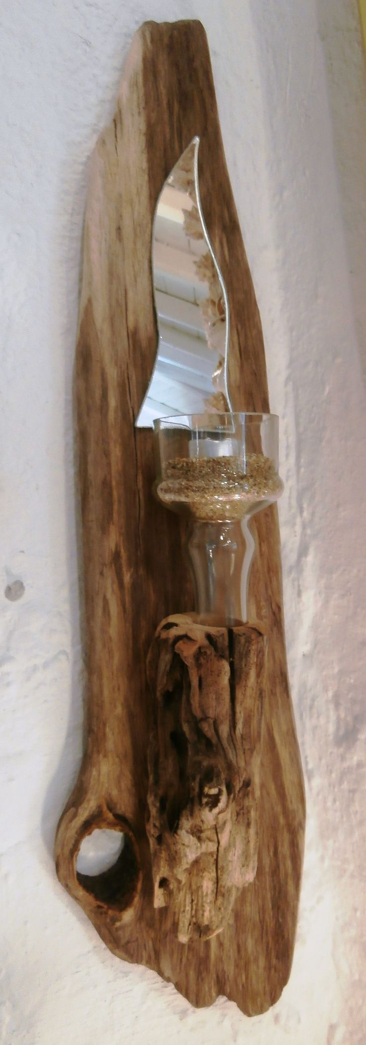 Driftwood wall sconce featuring the neck of a glass bottle, upturned to hold the tealight.