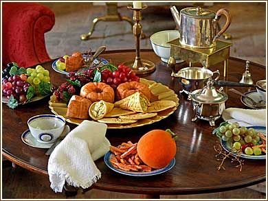 A tea table setting in the parlor of a wealthy 18th century family includes grapes and a faux sweetmeat dish with candied orange peels dusted with a coating of sugar. In the center is a dish the crispy-light wafers today called pizzelles and faux cornucopia-shaped cornets filled with rich egg custard. Created for the Camden County Historical Society. Photo: © copyright HistoricFauxFoods.com