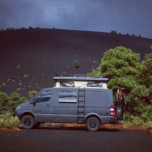 Pop top van camper with mountain bikes and more storage on top.