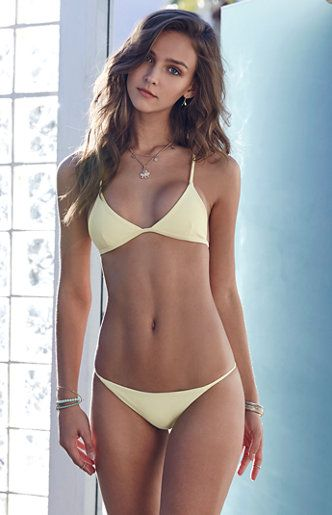 Online Only! Shake up your swim style with the Adventure Crisscross Back Fixed Triangle Bikini Top. This Kovey bikini top has a fixed triangle silhouette, solid yellow tone, plus chic crisscross back straps.   Fixed triangle bikini top Yellow wash Crisscross back straps Back hook closure Model is wearing a small Model's measurements: Height: 5'9.5'' Bust: 32'' Waist: 24.5'' Hips: 35'' Hand wash Made in California   Swim Retu...